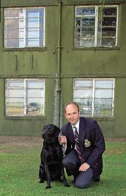 The editor with his black labrador Gibson outside of the former office (top right window) of Wg Cdr Guy Gibson VC DSO* DFC* at RAF Scampton. Mervyn Hallam